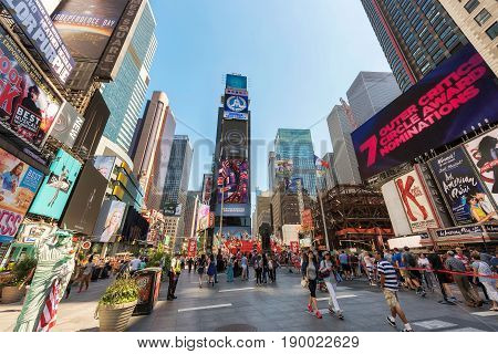 People walk through the famous Times Square on June 25, 2016 in New York, NY.  Times Square is a famous intersection in New York City.