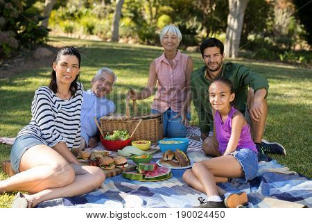 Portrait of happy family having picnic in the park on a sunny day
