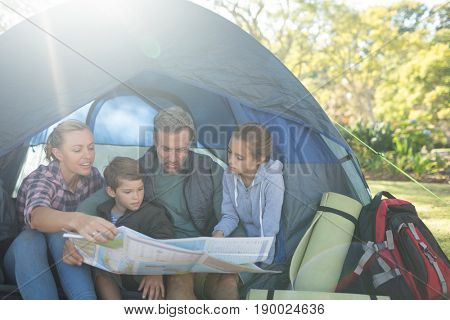 Family reading the map in tent on a sunny day