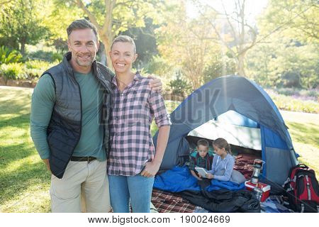 Couple smiling at camera while kids sitting in tent at campsite