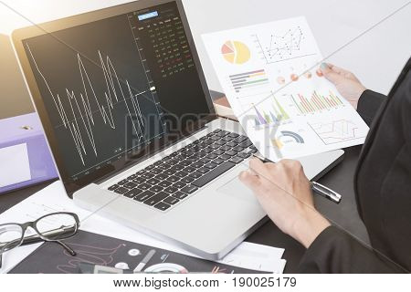 business hand working on computer notebook with Finance Trading Stock Graph Chart homepage on computer screen. invesment analysis concept.