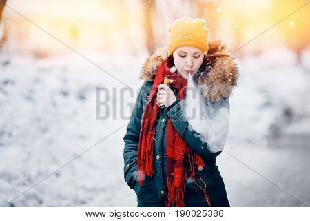 girl is holding an electronic cigarette in her hand and exhaling steam from her mouth. She is wearing a hat. Winter. Concept of safe smoking, giving up tobacco. Toning, highlighting