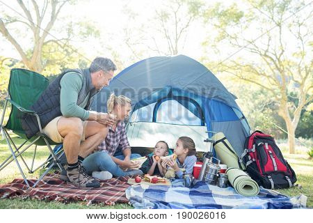 Family interacting while having snacks outside the tent at campsite poster