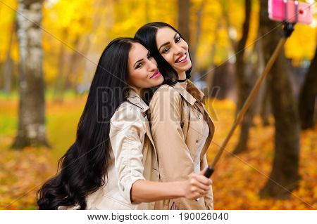 beautiful smiling brunette woman do selfie autumn