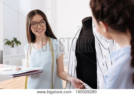 Pleasant socializing. Beautiful young woman wearing a measure tape over her neck, standing near the mannequin and holding a piece of cardigan hanging on it while looking at her colleague with a smile
