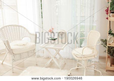 Beautiful modern veranda with cozy armchairs and coffee table