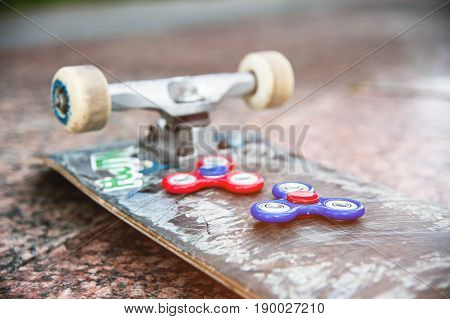 Close-up of skateboard and two spinners red and blue