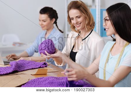 Here you go. Pleasant young woman passes a ball of purple thread to her colleague looking at it with smile.