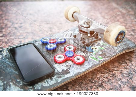 Close-up of skateboard and two spinners red and blue next to the phone on the skateboard