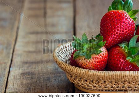 Fresh strawberries on wood background. Ripe strawberry in basket on rustic wood table. Copy space background of strawberry for your design.