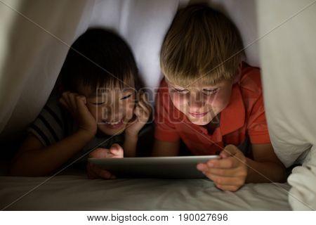 Siblings under bed sheet using digital tablet on bed in bedroom
