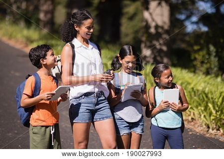 Happy students and teacher with digital tablets standing on street during summer field trip