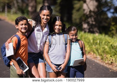 Portrait of happy teacher and children using digital tablets on street during summer field trip