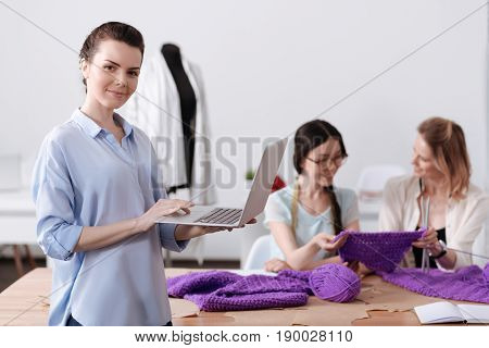 Enjoying themselves. Beautiful young woman holding a laptop and looking at the camera while her colleagues sitting at the table and holding a piece of knitwear.