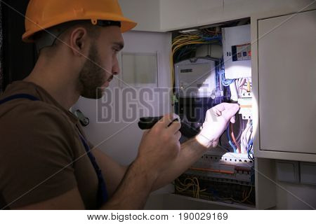 Young electrician with flashlight near switch box in dark room