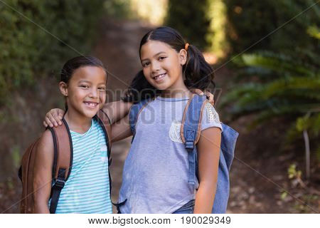 Portrait of smiling friends standing at natural parkland