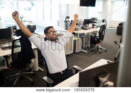 Happy businessman with arms raised sitting on chair in office