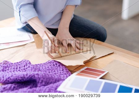 A future outfit. The focus being on dainty female hands holding a ruler and a pencil and drawing a line on a pattern.