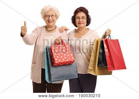 Two cheerful elderly women with shopping bags with one of them making a thumb up gesture isolated on white background