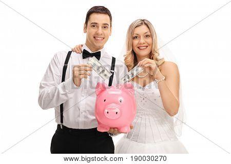 Newlywed couple putting money into a piggybank isolated on white background