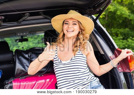 Travel, tourism - woman sitting in the trunk of a car with suitcases, showing thumb up sign, ready to leave for vacations
