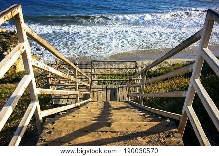 A wooden stairs leading down to the beach