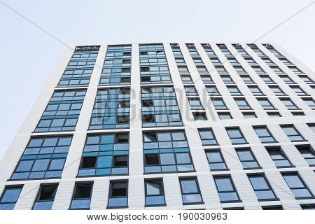 Skyscraper with glass facade. Modern building. Modern architecture. Transparent walls with small ajar windows reflecting bright blue sky. Abstract glass background.