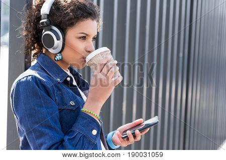 Lets have drink. Upbeat delighted charming young girl is holding smartphone and enjoying music through headphone while relaxing outdoors with hot coffee