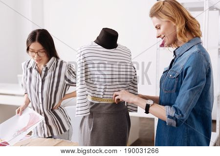 Perfect size. Charming young tailor measuring waist of a dress hanging on a mannequin and looking pleased with the result, while her colleague looking at a dress sketch