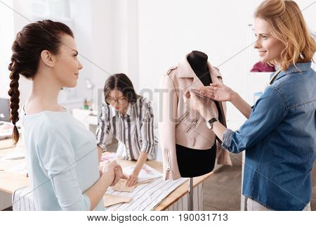 Best quality. Pleasant pretty tailor showing the quality of a lapel of the new jacket to her colleague while she listening to her attentively