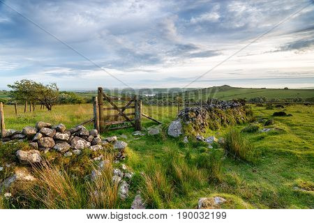 A wooden gate on Bodmin Moor in Cornwall leading out to Siblyback lake and Tregarrick Tor in the far distance