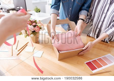 Customer care. The close up of dainty female hands packing a pink dress into a box, being ready to send it to the customer, while the other pair of hands holding a pink ribbon