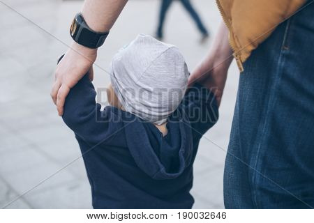 father and 1 year baby walk togather outside