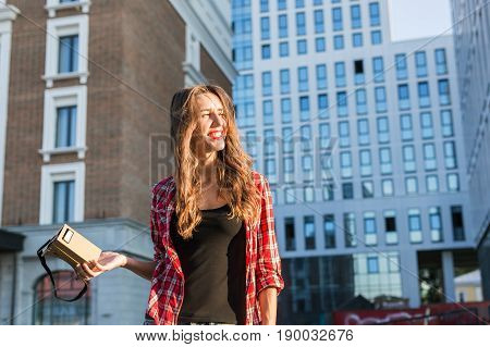 Beautiful young woman with long hair holds in hand virtual reality headset in an urban context.