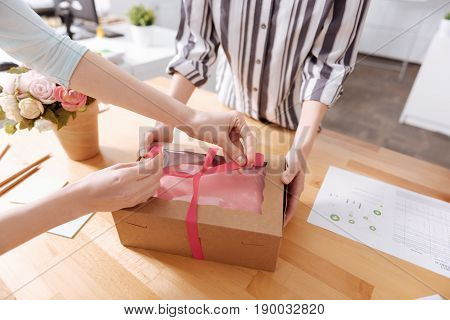 Everything for customers. Close up of a pair of beautiful female hands tying up a neat sophisticated bow on the box with a tailored dress while the other pair of hands holding the box
