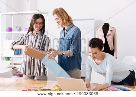 Best service. Two pleasant upbeat women packing a box with a dress into a blue bag while their colleague checking a destination on a laptop