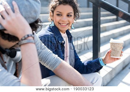 Happy smile. Portrait of charming mulatto girl is sitting on steps with her boyfriend. She is looking at him with love and holding cup of coffee. Focus on lady