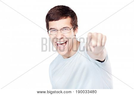 Young excited hispanic man wearing glasses and blue t-shirt standing and pointing at camera with his index finger isolated on white background - choice concept