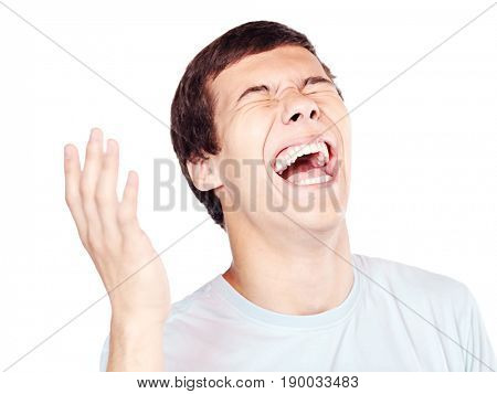 Close up of young hispanic man laughing out loud with closed eyes and hand near his head - laughter is best medicine concept