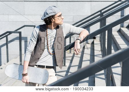 Contemplation. Profile of serious young guy is leaning on handrails while looking aside sadly. He is holding white skateboard