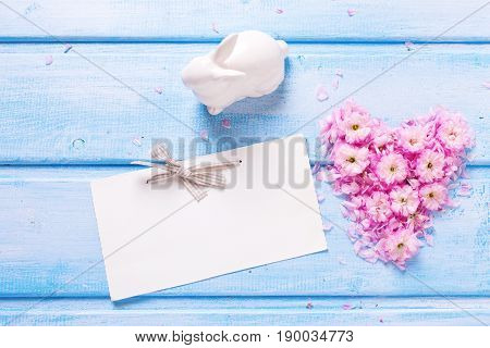 Heart from pink flowers and petals rabbit and empty tag on blue wooden planks. Selective focus. Place for text.