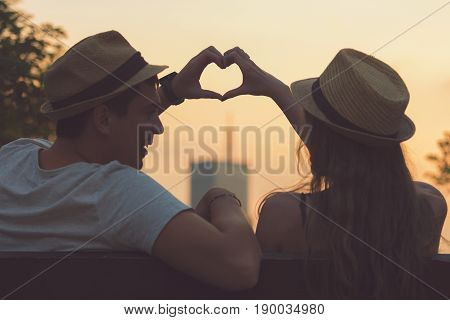 Couple in love making a heart - shape with hands.