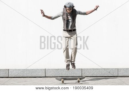 Jump shot. Energetic stylish teenager is doing trick on skateboard against white wall