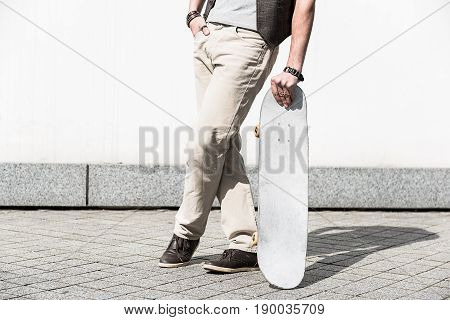 Enjoy little things. Close-up of crossed legs of young guy is standing against white wall and holding skateboard