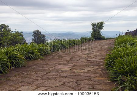 Curved empty plant lined paved walkway overlooking distant city and overcast sky landscape in Pietermaritzburg South Africa