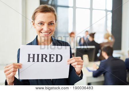 Young successful woman as entrant has new job and holds sign
