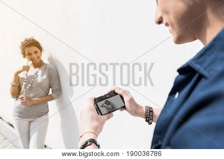 Nice shot. Cheerful young man is looking at camera in his hands while positive girl is posing against white wall. Focus on screen of photocamera