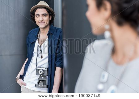 Love at first sight. Young positive lovers are standing outdoors. Selective focus on cheerful pleasant guy is looking at girl with smile while leaning on column