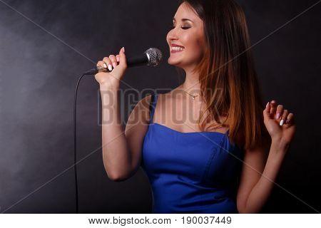 Singing brunette on black background