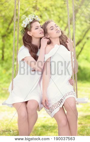 Two beautiful young women on swing in park